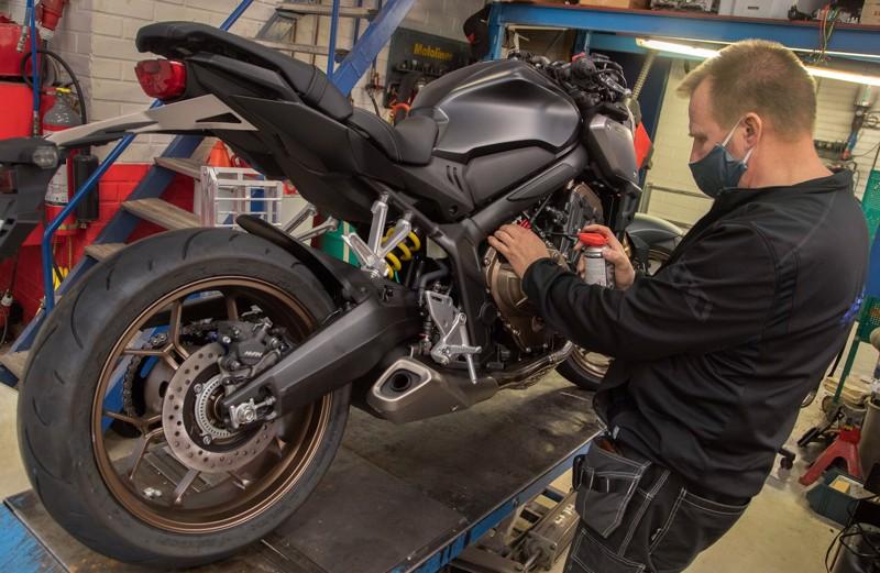 Moottoripyörän keväthuollossa on tärkeintä tarkistaa valojen, jarrujen ja renkaiden kunto sekä katsoa, ettei mistään vuoda öljyä, kertoo Veli-Pekka Ratinen. Parhaillaan Ratinen rasvaa kytkinvaijeria.