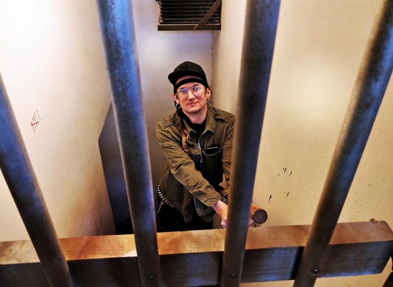 """Ron Rönnqvist seisoo kalterioven takana portaikossa, josta pakohuoneen peli alkaa. - Porukka """"herää"""" kaiteeseen kahlittuna ja heidän pitää alkaa selvittää mitä baari-illassa oikein tapahtui."""