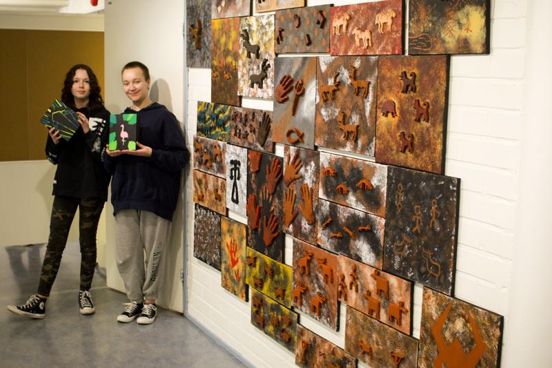 Viivi Koutonen (vas.) ja Saana Haikara olivat pystyttämässä Niva-Kaijan koulun ja Nivalan lukion kuvataidenäyttelyä. Koutonen ja Haikara poseeraavat tekemänsä laatikkotyöt käsissään. Vieressä perinteisiä kalliomaalauksia.