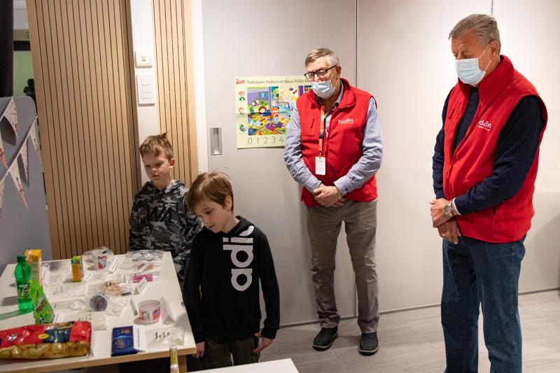 Veeti Heinoja, 7, ja Oliver Halme, 8, tutustumassa elintarvikkeiden sokerimääriin Eero Klemolan ja Timo Fältin johdolla.