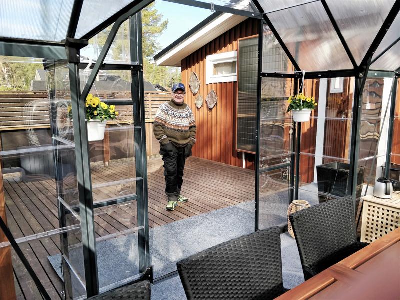 Muovinen kasvihuone terassilla palvelee kotoisana kahvittelu- ja oleskelutilana. Mökin seinustalla Leif Karlströmin itse  juomatölkeistä tekemä aurinkokeräin.