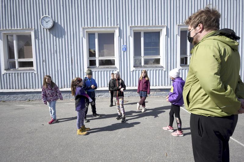 Marinkaisten koulun teatteriryhmäläiset patsastelevat koulun pihalla yhdessä kerhon ohjaaja Esko Tynkkysen kanssa.