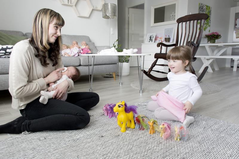 Mervi seuraa vauvan kanssa Ellenin ponileikkejä. Tytön omat vauvat ovat kiltisti sohvalla.