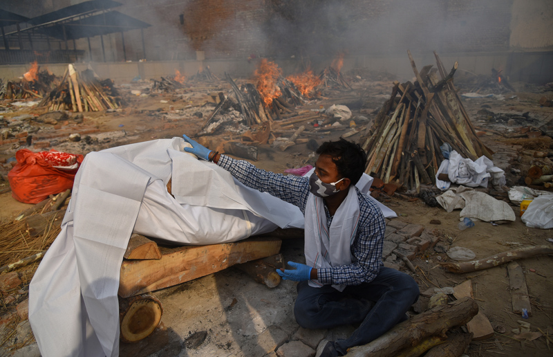 Lähes puolet maailman uusista koronatartunnoista ja joka neljäs koronakuolema raportoitiin tällä viikolla Intiassa. Omaiset tekivät viimeisiä rituaaleja koronasairauden uhrille krematointikentällä Delhissä 29. huhtikuuta 2021.