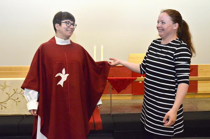 Kirkkoherra Eija Nivala sovittaa tekstiilitaiteilija Silja van der Meerin tekemää kasukkaa.
