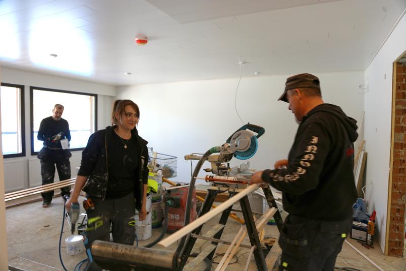 Aira Häiväläinen (keskellä) valmistautuu käyttämään paineilmanaulainta. Mika Skantsi (oik.) sirkkelöi listoja ja taustalla Murhaf Bakkar maalaa listoja. Rivitalon remontin on tarkoitus valmistua alkukesästä.