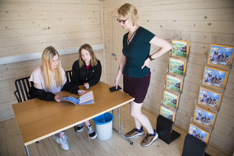 Kesätyöntekijät Tiia Lehtonen (vas.) ja Venla Palola sekä kulttuuriohjaaja Anna-Maria Oja ehtivät alkuviikon aikana muuttaa ennakkoäänestyspaikkana toimineen rakennuksen infopisteeksi.