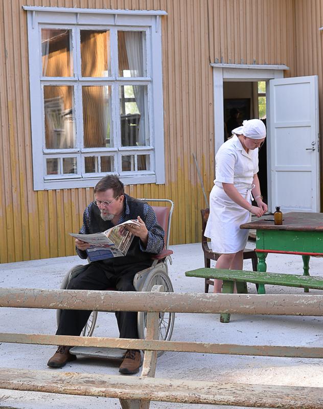 Vanha Troberg (Jukka Puranen) lukee hoitajalle (Senni Kokkoniemi) lehdestä Reisjärven kuntavaalituloksia. -Mitähän sinne Reisjärvelle kuuluu? Troberg kyselee raahelaisessa vanhainkodissa.