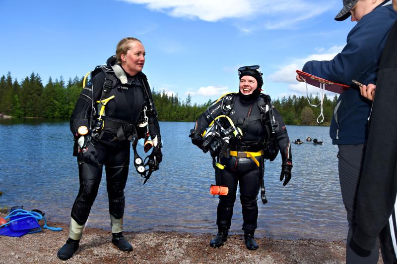 Miia-Maria Lehtola (oikealla) kirjaa heti nousun jälkeen muistiin tiedot Satu Hartikaisen (vasemmalla) ja Sannukka Lumiahon sukelluksesta, muun muassa hapen kulutuksesta. Niin he pystyvät suunnittelemaan paremmin tulevia sukelluksia.