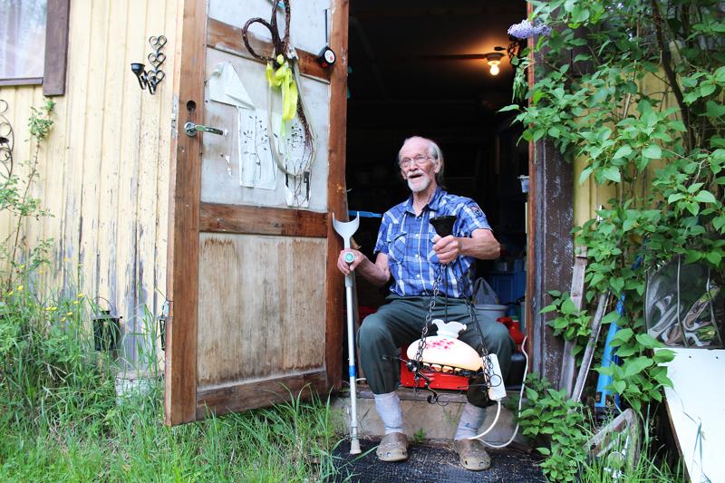 Vanhan autotallin kynnyksellä Vilho Ojala takoo rautaa ja miettii uusia malleja. Ovessa on tilaa mallipiirustuksille.