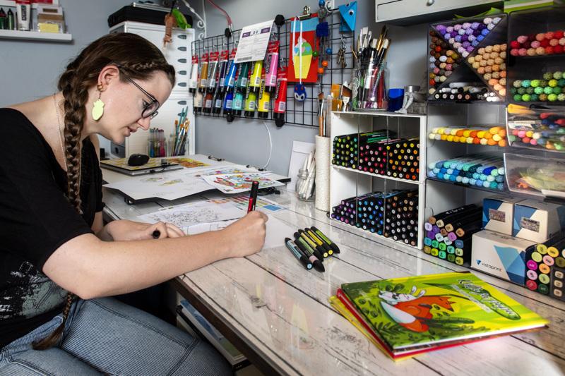 Tanja Hietala viimeistelee neljännen satukirjansa kuvituksia työhuoneessaan. Pöydällä on pinossa hänen aiemmin julkaisemiaan kirjoja.