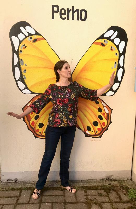 Olga Melet-Pajuoja maalasi Perhon kunnanviraston seinään perhosen, jonka edessä voi käydä nappaamassa itsestään selfien.