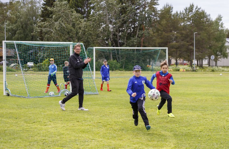 Frans Somero ja Perttu Pentti tavoittelevat palloa K-Pallon Teholeirillä. Leirin päävalmentaja Kari Laukkanen kannustaa taustalla.