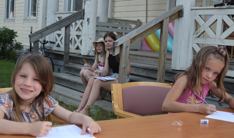 Lapset hakivat piirrosmallinsa Pappilan pihalta. Vasemmalta Taika ja Aava, taustalla Anni ja Aada.