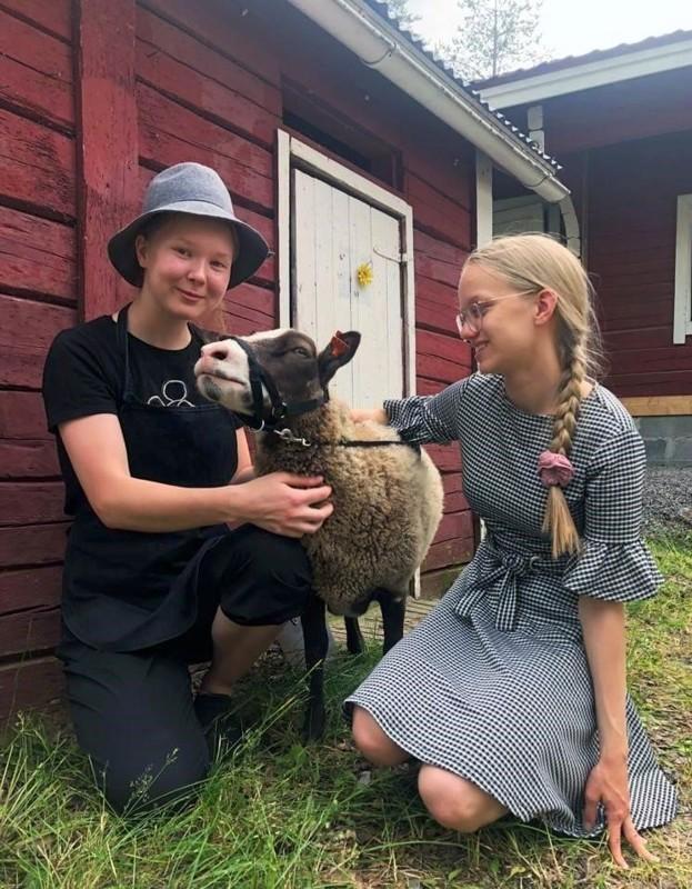 Kuluvan kesän kesäkahvilayrittäjät Mirjami Mäkinen (vas.) ja Julia Humalajoki sekä kahvilakävijöitä perinnepäivänä tervehtinyt Riemu-lammas.
