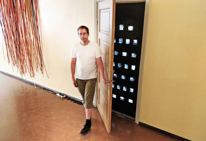 Hans G. Hästbackan Black Kaffinobox XXI - valokuvainstallaatio on piilotettuna oven taakse.