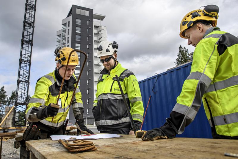 Raudoittaja Saku Erkkilä, työnjohtaja Christian Huldén ja kirvesmies Miika Laasanen Pikiruukin Luotsi-tornitalon rakennustyömaalla.