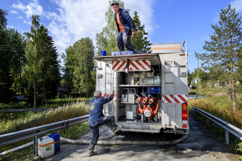 Pohjois-Savon pelastuslaitoksen vanhemmat sammutusmiehet Reijo Kiimalainen (alhaalla) ja Janne Haatainen kävivät imemässä vettä Vääräjoesta.