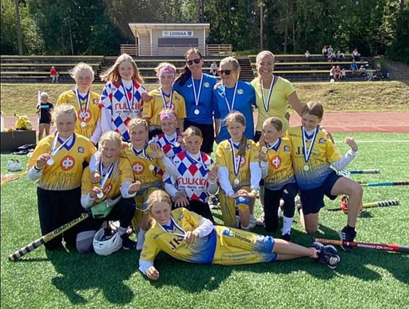 Iloinen Oulaisten Huiman E-pesistyttöjen hopeajoukkue valmentajiensa kanssa yhteiskuvassa pelin jälkeen.