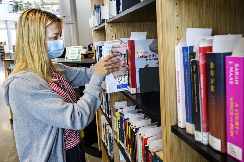 Kokkolan kirjaston työntekijä Fanny Paananen laittaa varattuja kirjoja varaushyllyyn. Paananen kertoo, että hän itse lukee mieluiten dekkareita.