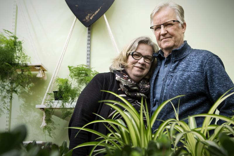 Hautausalan yrittäjät Riitta ja Reijo Laurila ovat kasvaneet työhönsä yrittäjävuosien aikana. Taustalla näkyy perinteinen kasvi unelma eli plumosus.