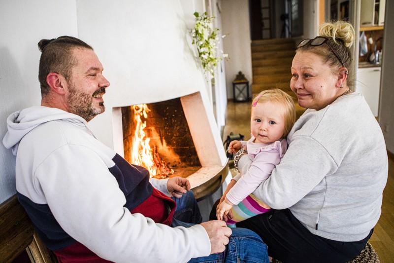 Mika Pajuniemen ja Satu Uraston lapsenlapsi Emma Leinonen nauttii takkatulen lämmöstä.
