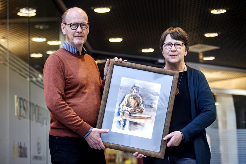 Heikki Nisonen ja Riitta Rauhala esittelevät yhtä arpajaispalkinnoista: Esa Tiaisen akvarellia.
