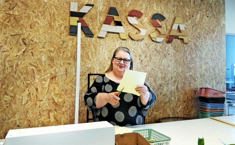 Ohjaaja Tiina Kultalahti-Byskata leikkaa lisää hintalappuja entisen Retron, nykyisen Asema Luotsin kierrätyskaupassa Jaakonkadulla.