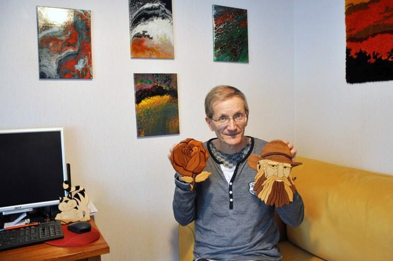 Heikki Moilanen tekee muun muassa eri puulajeja yhdistelmällä tauluja. Seinällä näkyy hänen akryylitöitään.