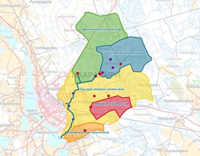 Kartassa Tujunojan osavaluma-alueet eri väreillä. Tujunoja on merkitty sinisellä viivalla ja rakennettuja vesiensuojelurakenteita on merkitty punaisella (laskeutusaltaat) ja violetilla (muut rakenteet) pisteellä.