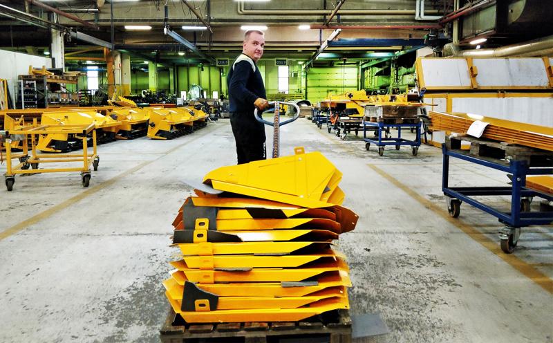 Marko Murtoniemi kuljettamassa niittomurskaimeen kuuluvia sisäpeltejä. Pietarsaaresta kotoisin oleva Murtoniemi on työskennellyt Elholla kaksikymmentä vuotta.