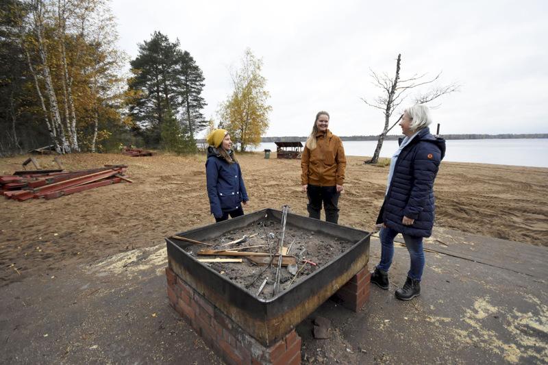 Laajalahden vanha grillikatos on jo hävitetty. Tilalle tulee uusi isompi keittokatos penkkipöytineen ja  nykyaikaisine grillauspaikkoineen. Katoksen edustalle tulee toinen grillipaikka ja pitkin rantaa pari lisää. Kuvassa Rosanna Telaranta (vas.), Sini Sangi ja Lotta Nyqvist.