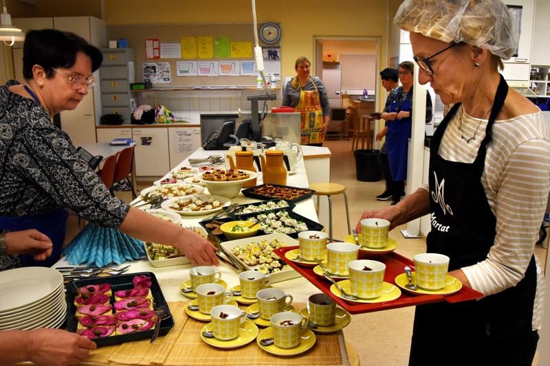 Noutopöytä valmistui nopeasti porukalla. Tuija Metsäharju asettelee tarjolle särkisäilykkeestä tehtyjä särkimousseleipiä, Leila Särkipaju kahvikupeista tarjottuja maa-artisokkacappuchinoja.