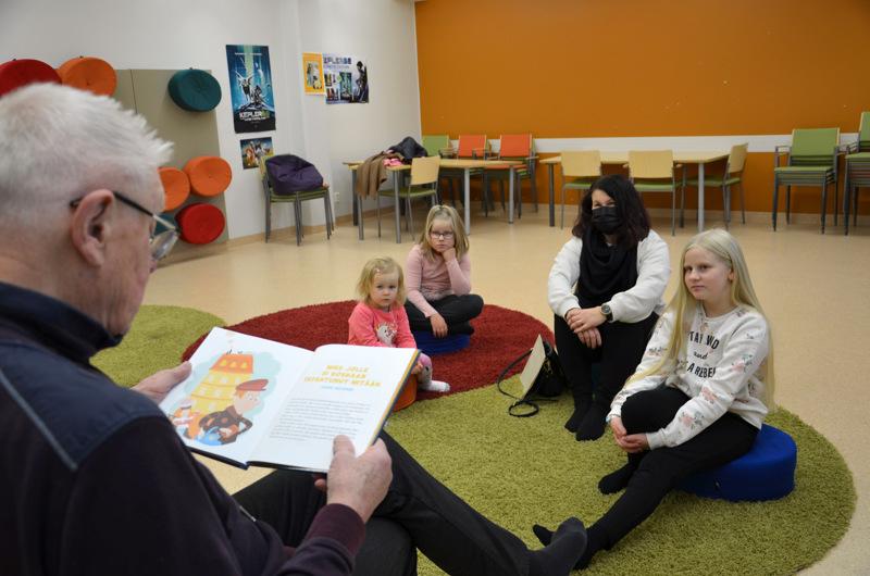 Jormis lukee satuja. Enni Rautiola, Liisa Järnbäck, Paula Järnbäck ja Anni Järnbäck kuuntelevat tarkasti.