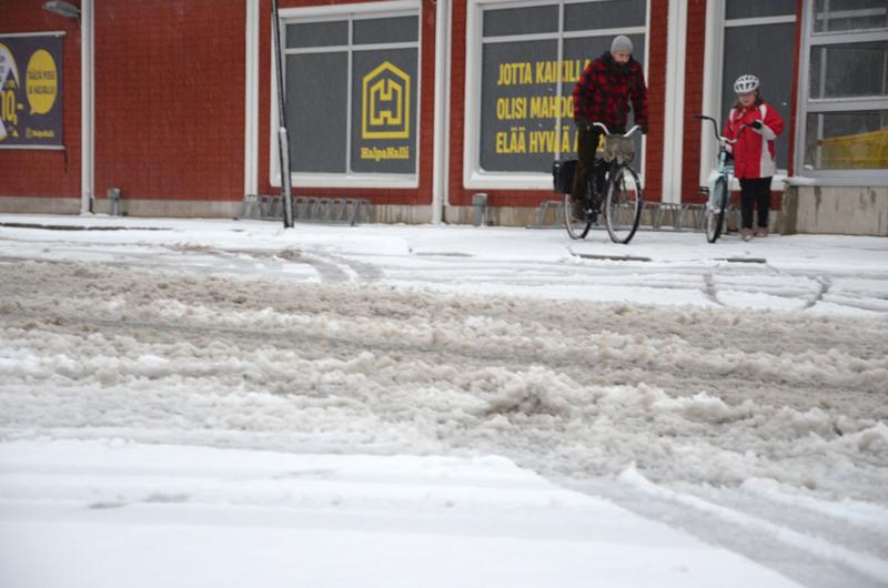 Yöllä satanut lumi solskuuntuu ajoväylälle ja haittaa myös pyöräilijöitä ja jalankulkijoita.