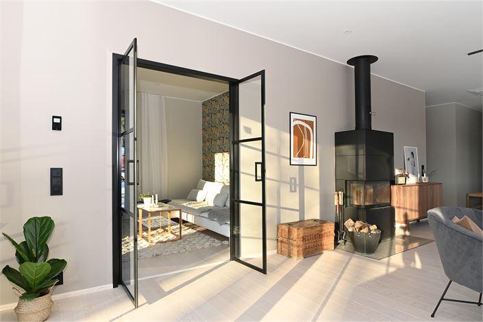 Harkittuja mustia yksityiskohtia: Koko kodissa on mustat pistorasiat ja valokatkaisijat, olohuoneessa musta takka ja lasipariovet tuovat sopivasti särmää muuten luonnonläheisiin väreihin.