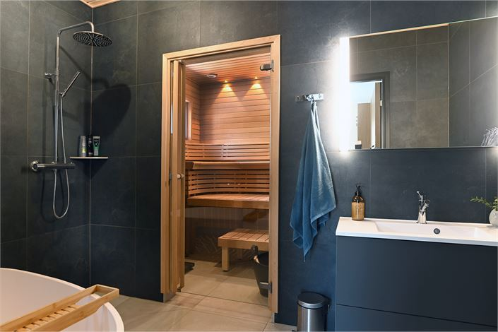 Mustat kaakelit sopivat hyvin yhteen saunan tervaleppäpaneelien ja lauteiden kanssa.