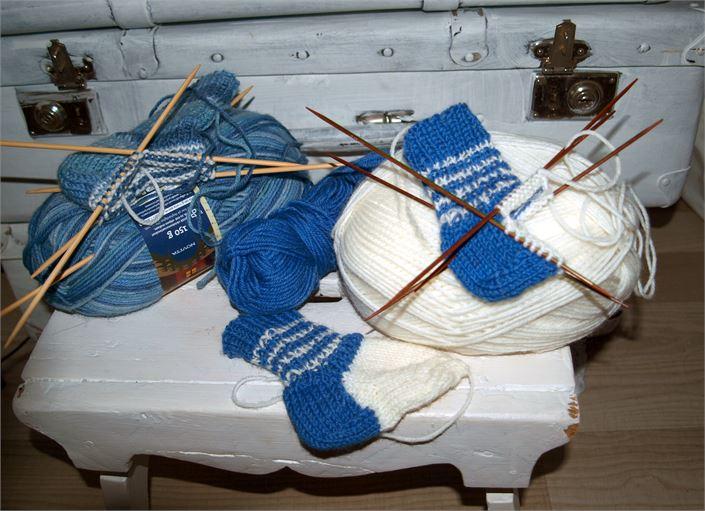 Sinivalkoisia sukkia on kudottu jo paljon tämän vuoden vauvoille. Kuva: Hilla Jumeri