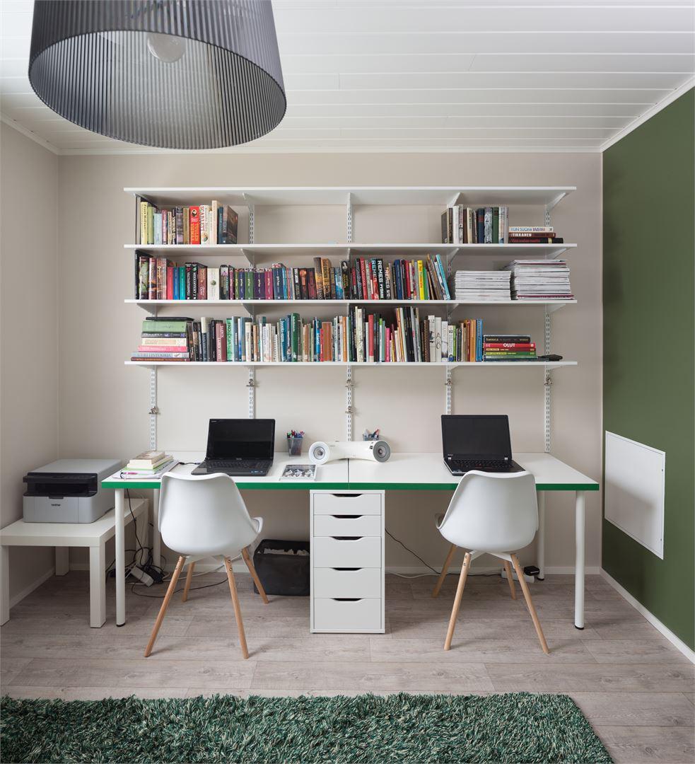 Tässä huoneessa on tilaa kirjoille ja työskentelylle.