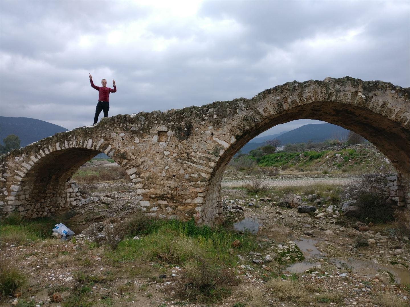 Pariskunta ei käytä moottoriteitä, joten tanssiminen vanhalla sillalla keskellä Kreikan maaseutua onnistuu vaivatta.