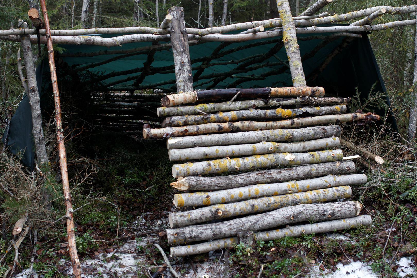 Hetken kuluttua kasaamme tulisijan suojaksi lämpöä heijastavan puupinon.