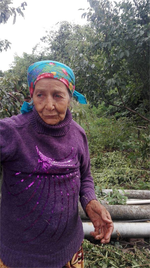 Бабушка Маша. Показывает где был похоронен сын. Прямо в саду.